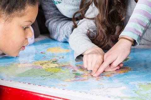 Kinder zeigen auf einer Weltkarte mit ihren Fingern auf Bayern.